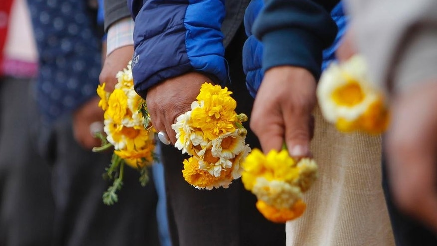 Supporters carry flowers as they wait for their turn to pay respect to Surya Bahadur Thapa, who served as Nepal's prime minister five times, at Dashrath Stadium in Kathmandu, Nepal, Friday, April 17, 2015. Thapa, died in a hospital in India where he was being treated for stomach cancer. He was 87. (AP Photo/Niranjan Shrestha)