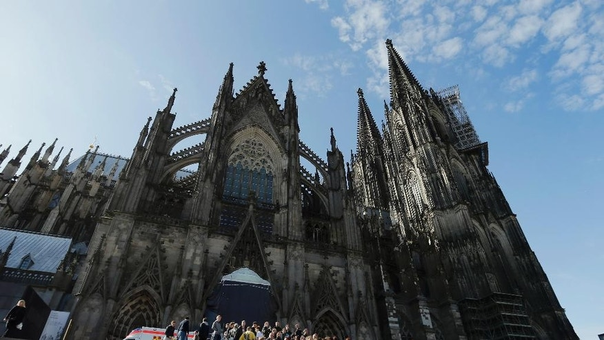 People queue in front of the Cologne Cathedral in Cologne, Germany, Friday, April 17, 2015. A mourning ceremony will be held in the Cathedral  in memory of the 150 victims of the Germanwings plane crash last month in the French Alps. (AP Photo/Frank Augstein)