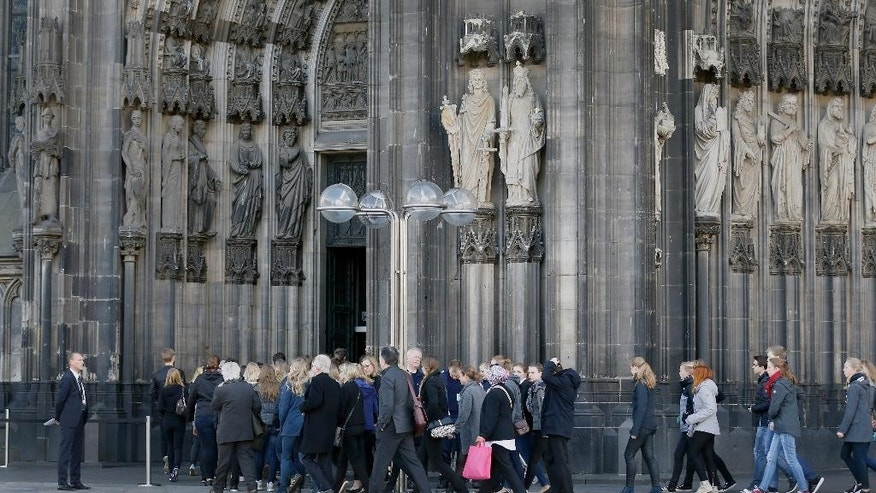 People enter the Cologne Cathedral in Cologne, Germany, Friday, April 17, 2015. A mourning ceremony will be held in the Cathedral  in memory of the 150 victims of the Germanwings plane crash last month in the French Alps. (AP Photo/Frank Augstein)