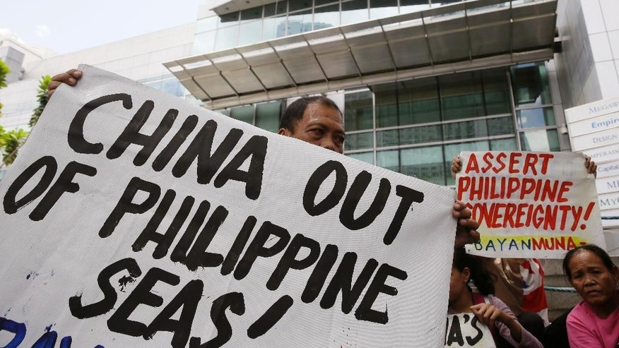 "Protesters display placards during a rally at the Chinese Consulate at the financial district of Makati city east of Manila, Philippines Friday, April 17, 2015 to protest against Beijing's land reclamation activities on disputed territory in the South China Sea. The protesters led by Congressman Nery Colmenares urge China to ""stop its reclamation activities in the Mischief Reef"" which they claim to be still within the Philippines' EEZ (Exclusive Economic Zone). (AP Photo/Bullit Marquez)"
