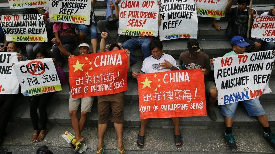 "Protesters display placards during a rally at the Chinese Consulate at the financial district of Makati city, east of Manila, Philippines Friday, April 17, 2015 to protest moves by China in ""fortifying"" its claims at the disputed Spratlys group of islands in the South China Sea. The protesters led by Congressman Nery Colmenares urge China to ""stop its  reclamation activities in the Mischief Reef"" which they claim to be still within the Philippines' EEZ (Exclusive Economic Zone). (AP Photo/Bullit Marquez)"