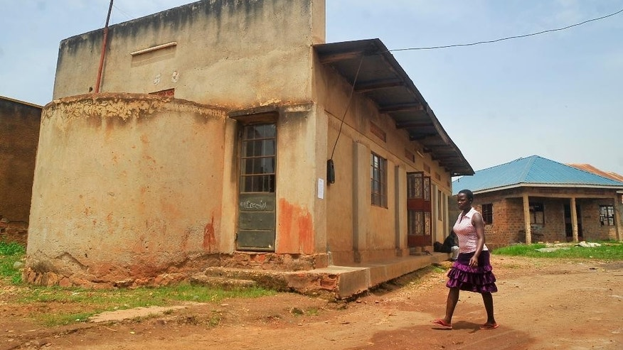 In this photo taken Tuesday, April 14, 2015, a woman walks past the Masjid Taqwa mosque in the Zana suburb of Kampala, Uganda. A crackdown by Ugandan police on suspected Islamic extremists has sent a current of fear through the Islamic community in Uganda, especially in the Masjid Taqwa mosque whose imam, former Guantanamo Bay prisoner Jamal Kiyemba, was recently arrested. (AP Photo)