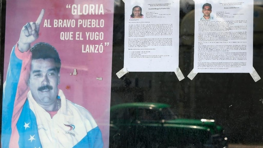 The biographies of two candidates running for election are taped to a window next to a poster of Venezuela's President Nicolas Maduro in Havana, Cuba, Friday, April 17, 2015. President Raul Castro began slow-moving but wide-ranging reforms in Cuba's centrally planned economy in 2010, and has promised changes to the electoral system but provided no details to date. (AP Photo/Desmond Boylan)