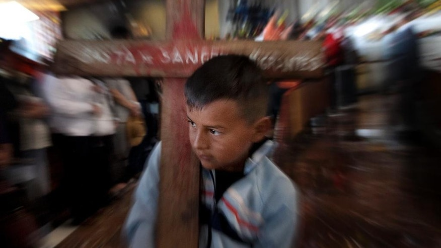 "A young boy carries a cross with a message that reads in Spanish; ""Enough of the shedding of immigrants' blood,"" during a Mass at the the Basilica of Guadalupe, in Mexico City, Saturday, April 18, 2015. A group of Central American migrants, who made a pilgrimage to the Basilica Saturday, is caravanning through Mexico asking for greater protection for transiting migrants. Tens of thousands of migrants have disappeared while making their journey through Mexico, where they are vulnerable to extortion and abuse by both police and criminal gangs. (AP Photo/Marco Ugarte)"