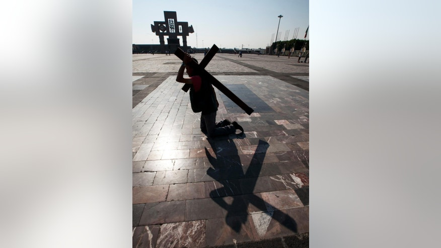 A Central American migrant bears a cross while walking on his knees to the entrance of the Basilica of Guadalupe, in Mexico City, Saturday, April 18, 2015. The group is caravanning through Mexico asking for greater protection for transiting migrants. Tens of thousands of migrants have disappeared while making their journey through Mexico, where they are vulnerable to extortion and abuse by both police and criminal gangs. (AP Photo/Marco Ugarte)