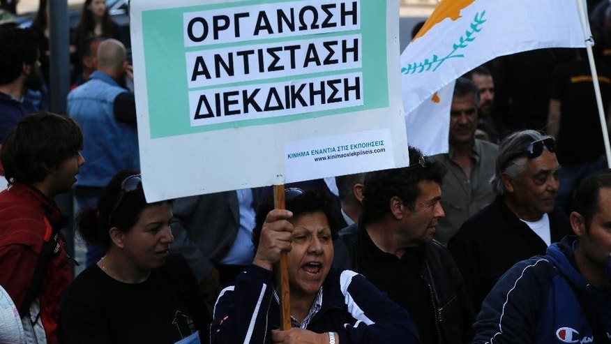 "A protester shouts under a banner that reads: ""Organization, Resistance, Claiming"", during a demonstration outside Cyprus' Parliament in the capital Nicosia on Friday, April 17, 2015. Several dozen protesters gathered outside parliament to voice their opposition to legislation that would make it easier for banks to go after a huge number of bad loans. More than half of all loans in Cyprus have gone sour in the wake of the country's March 2013 rescue deal that resulted in high joblessness and slashed salaries. (AP Photo/Petros Karadjias)"