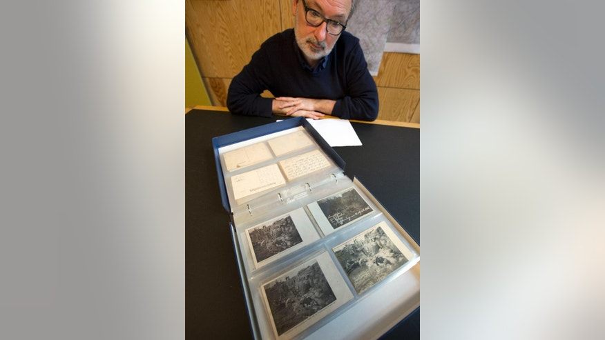In this photo taken on Thursday, April 9, 2015, director of the In Flanders Fields Museum Piet Chielens looks at postcards of victims of the first gas attacks of World War I, during an interview in his office at the museum in Ypres, Belgium. Chlorine gas - sent crawling in favorable winds over Flanders Fields from German positions - sowed terror and agony for the first time on April 22, 1915. The era of chemical weaponry had dawned. The weapon of mass slaughter came to symbolize the ruthlessness and, many say, futility of the 1914-1918 Great War.  Many Allied soldiers who fell victim to the first gas attacks in 1915 were photographed by German soldiers and transformed into postcards to send back to the homefront. (AP Photo/Virginia Mayo)