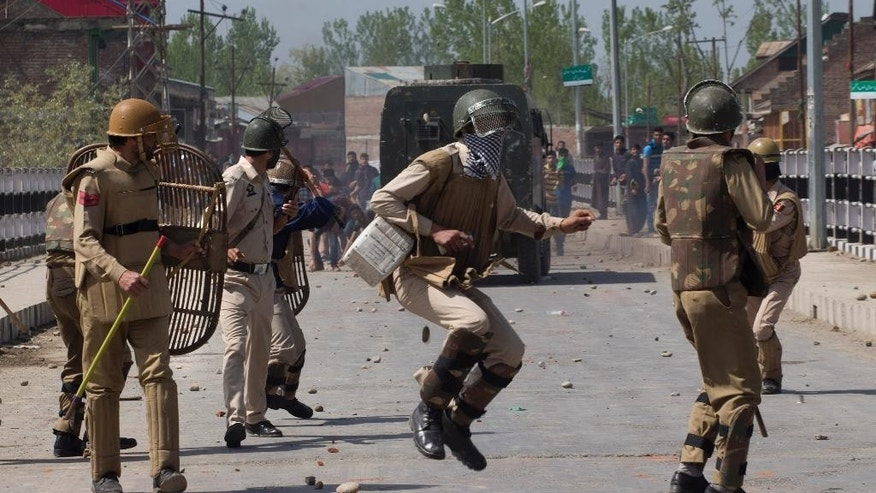 An Indian policeman jumps to avoid a stone thrown at him by Kashmiri protesters in Narbal, some 15 Kilometers (10 miles) North of Srinagar, Indian controlled Kashmir, Saturday, April 18, 2015. Government forces fired on anti-India protesters Saturday and killed a teenage student on the second day of violent clashes in the disputed Himalayan region, police said. Relatives disputed the official account, saying the boy was killed in custody. In an unusual move for law enforcement in Kashmir, police quickly opened a case for murder and began investigating the boy's death. (AP Photo/Dar Yasin)