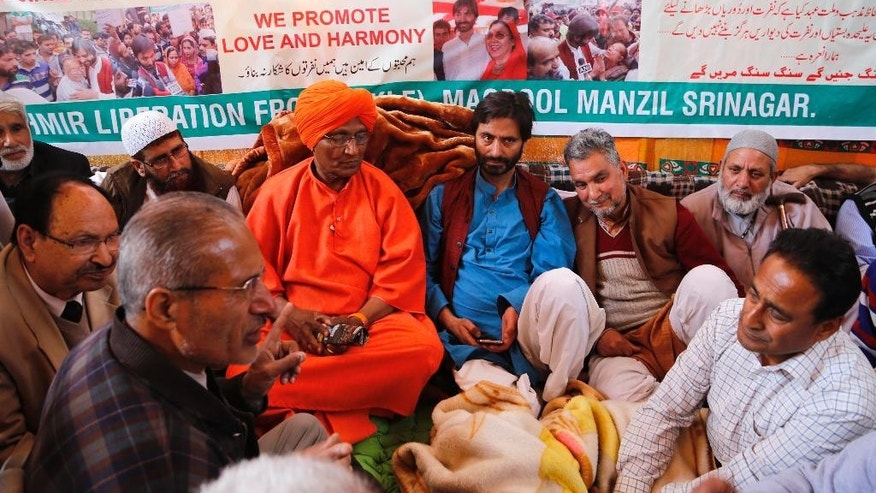 Chairman of the Jammu Kashmir Liberation Front (JKLF) Yasin Malik, center wearing blue, sits for a 30-hour- long hunger strike, with social activist Swami Agnivesh, in saffron robe, sitting in support in Srinagar, Indian controlled Kashmir, Saturday, April 18, 2015.  Malik along with his supporters began a 30-hour hunger strike to protest India's plan to build townships for Hindus who fled a rebellion in Muslim-majority areas. (AP Photo/Mukhtar Khan)