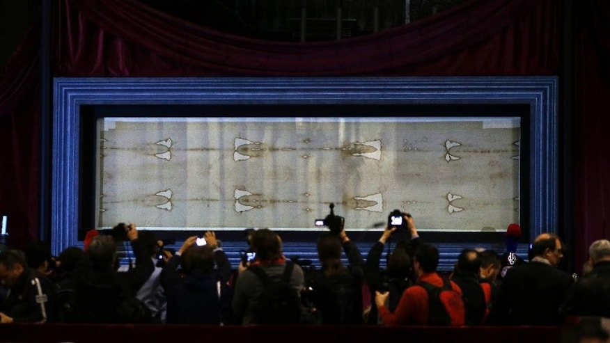 The Holy Shroud, the 14 foot-long linen revered by some as the burial cloth of Jesus, is on display during a preview for the press at the Cathedral of Turin, Italy, Saturday, April 18, 2015. The long linen with the faded image of a bearded man, that is the object of centuries-old fascination and wonderment, will be on display for the public from April 19 to June 24, 2015. Pope Francis said he is planning to visit the Holy Shroud during a a pilgrimage to Turin next June 21, 2015. (AP Photo/Antonio Calanni)