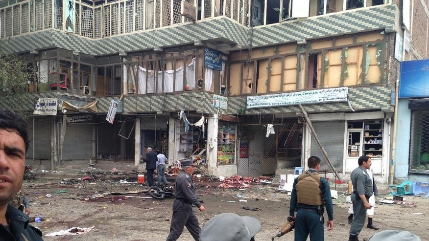 Afghan security forces inspect the site of a suicide attack near a bank branch in Jalalabad, east of Kabul, Afghanistan, Saturday, April 18, 2015. The suicide bomb attack on the bank branch has killed dozens of people, officials said. (AP Photo)
