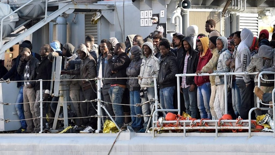 """Migrants stand on the deck of the Italian Navy ship """"Driade"""" prior to being disembarked in Messina's port, Sicily, Italy, Saturday, April 18, 2015. Italian ships have picked up some 10,000 people, many of them refugees of war and persecution, over the past week, an unprecedented number in such a short period. The influx is putting pressure on Italy's shelter system and raising calls for a better response to the emergency. (AP Photo/Carmelo Imbesi)"""
