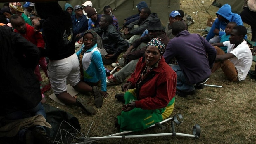 Refugees wait to be settled at a temporary refugee camp set up for foreign nationals fleeing attacks from South Africans in, In Johannesburg, South Africa Saturday, April 18, 2015. Mobs in South Africa attacked shops owned by immigrants in poor areas of the city overnight following similar violence in another part of the country that killed six people, according to media reports. (AP Photo/Denis Farrell)