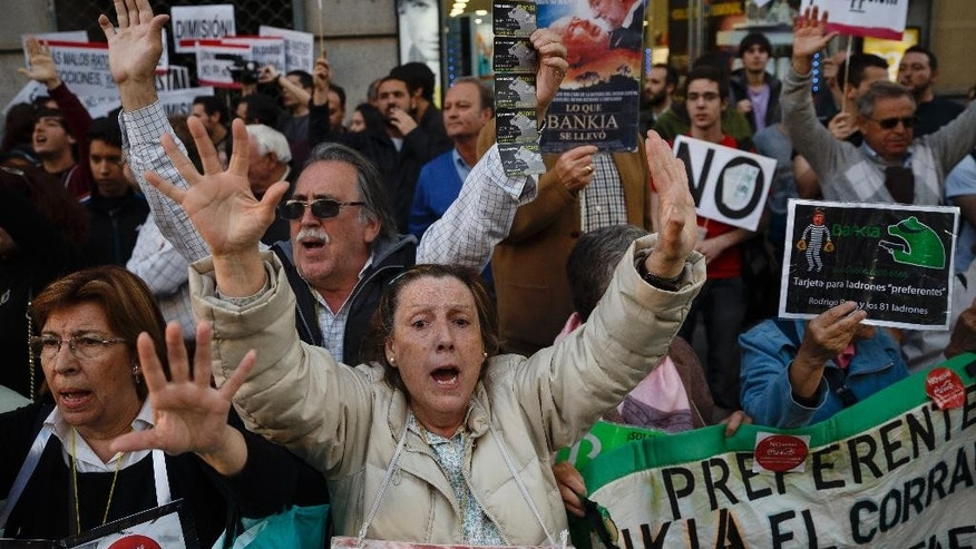 Protestors shout against corruption during a demonstration in Madrid, Spain, Friday, April 17, 2015. Former Finance Minister and International Monetary Fund chief Rodrigo Rato said Friday April 17, 2015, he plans to cooperate with justice officials after being detained for several hours while investigative tax agents searched his apartment and an office in Madrid. A spokesman for Madrid's justice tribunal said Rato was under investigation by Madrid prosecutors for fraud, money laundering and asset concealment. (AP Photo/Daniel Ochoa de Olza)