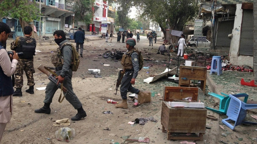 April 18, 2015: Afghan security forces members inspect the site of a suicide attack near a new Kabul Bank in Jalalabad, east of Kabul, Afghanistan.
