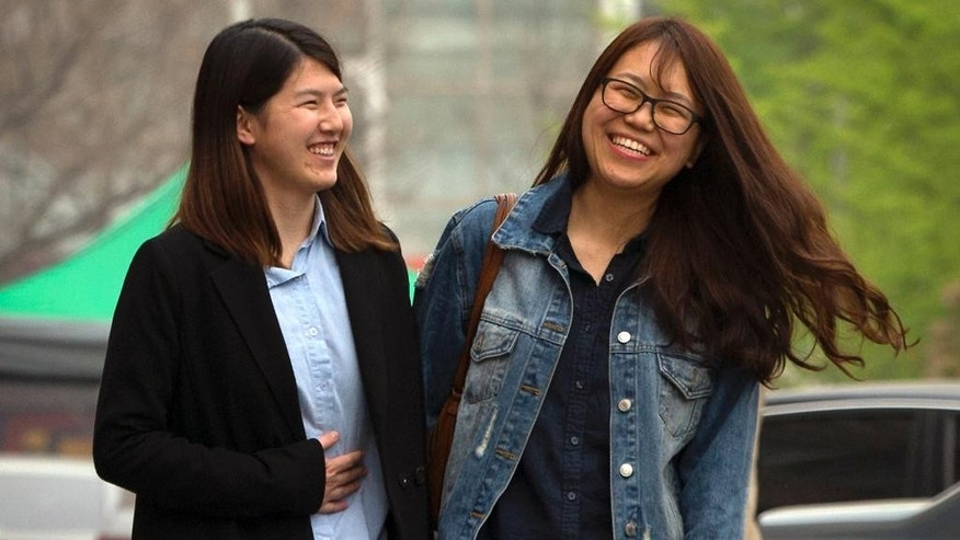 In this April 18, 2015 photo, Chinese activist Li Tingting, left, and her girlfriend, who wished to be identified only by her English name of Teresa, laugh as they walk along a street in suburban Beijing. Li, one of five recently released Chinese women's rights activists feels her dedication to activism has grown only stronger after spending 37 days in detention with interrogators who blew smoke onto her face and insulted her sexual orientation, her girlfriend and her lawyer said. (AP Photo/Mark Schiefelbein)