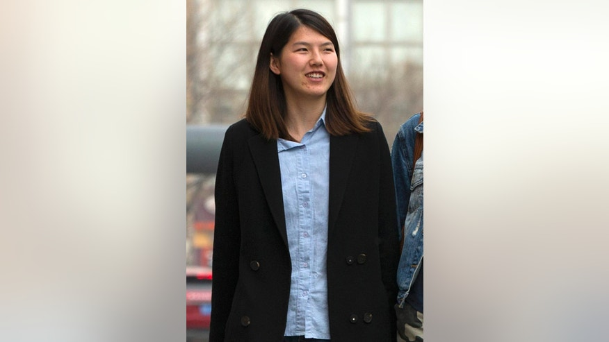 In this April 18, 2015 photo, Chinese activist Li Tingting, walks along a street in suburban Beijing. Li, one of five recently released Chinese women's rights activists feels her dedication to activism has grown only stronger after spending 37 days in detention with interrogators who blew smoke onto her face and insulted her sexual orientation, her girlfriend and her lawyer said. (AP Photo/Mark Schiefelbein)
