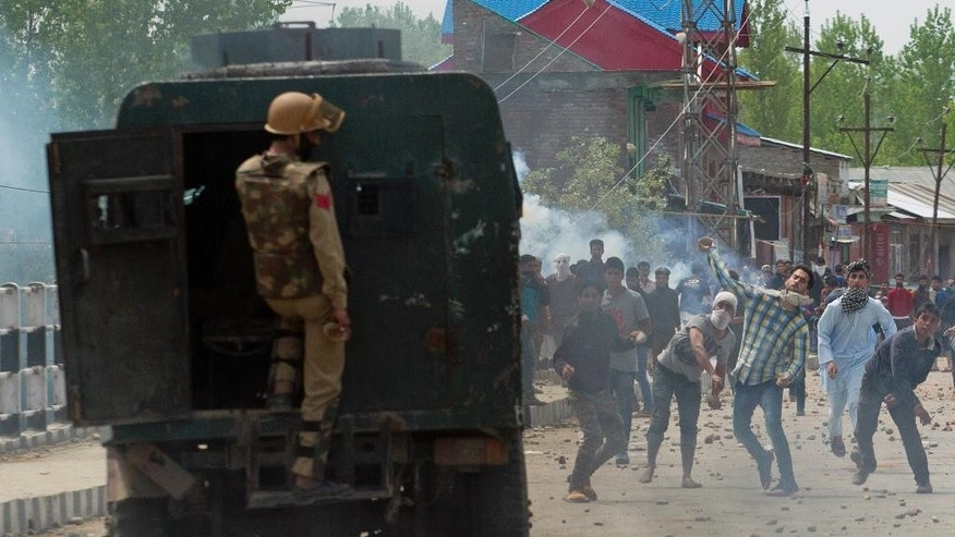 An Indian policeman takes cover behind an armored car as Kashmiri protestors hurl rocks and bricks in Narbal, some 15 Kilometers (10 miles) North of Srinagar, Indian controlled Kashmir, Saturday, April 18, 2015. Government forces fired on anti-India protesters Saturday and killed a teenage student on the second day of violent clashes in the disputed Himalayan region, police said. Relatives disputed the official account, saying the boy was killed in custody. In an unusual move for law enforcement in Kashmir, police quickly opened a case for murder and began investigating the boy's death. (AP Photo/Dar Yasin)