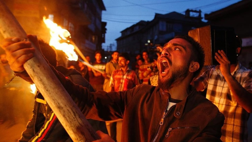 Activists of Jammu and Kashmir Liberation Front (JKLF) shout freedom slogans as they participate in a torch light procession in Srinagar, India, Saturday, April 18, 2015. Dozens of JKLF supporters participated in a torch light procession against the killing of a teenage student in Indian controlled Kashmir on Saturday. (AP Photo/Mukhtar Khan)