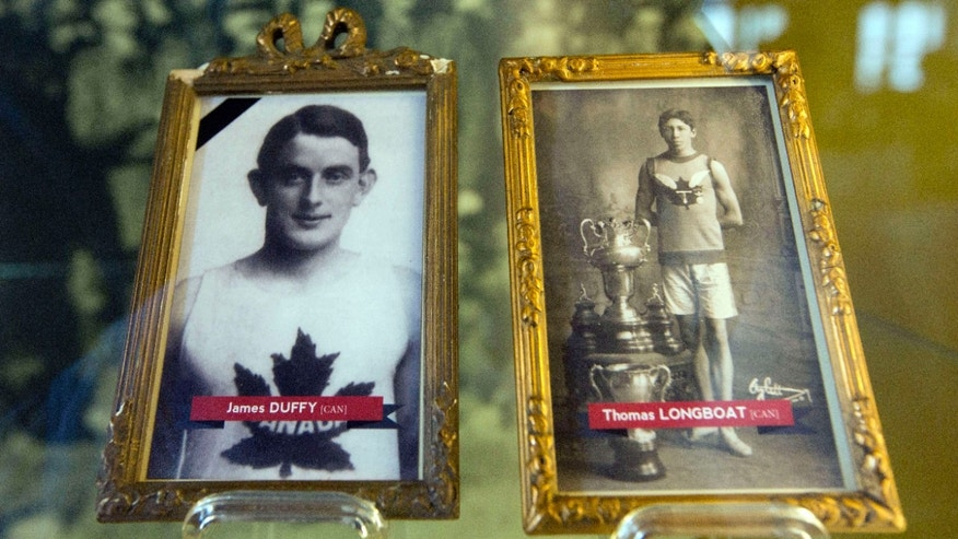 June 14, 2014: In this photo illustrations of World War I soldiers and Boston Marathon winners James Duffy, 1914, and Tom Longboat, 1907, are framed behind glass on exhibit at the In Flanders Fields Museum in Ypres, Belgium.