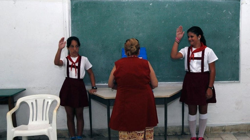 School children salute as a woman casts her ballot during Cuba's municipal elections at a polling station in Havana, Cuba, Sunday, April 19, 2015. Cuba held its first local elections since a historic thaw in relations with the United States with an unusual wrinkle in the single-party system: two of the 27,000 candidates openly oppose the government. (AP Photo/Desmond Boylan)
