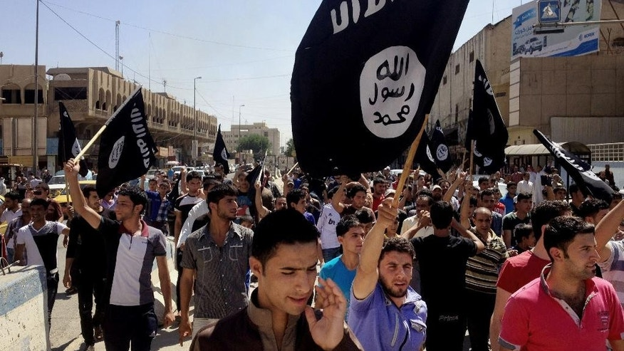 FILE - In this Monday, June 16, 2014 file photo, demonstrators chant pro-Islamic State group slogans as they wave the group's flags in front of the provincial government headquarters in Mosul, 225 miles (360 kilometers) northwest of Baghdad, Iraq. (AP Photo, File)