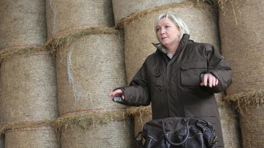 FILE - In this March 20, 2015 file photo, French far right leader Marine Le Pen adresses farmers while visiting a farm as she campaigns for local elections in Normandy, France. A pact of sorts may end the bloodletting between Le Pen and her 86-year-old father, Jean-Marie Le Pen, a party founder whose latest anti-Semitic remarks have tripped up the efforts of his daughter to give the National Front a new look. She announced on national television she will oppose his candidacy in December regional elections. (AP Photo/David Vincent, File)