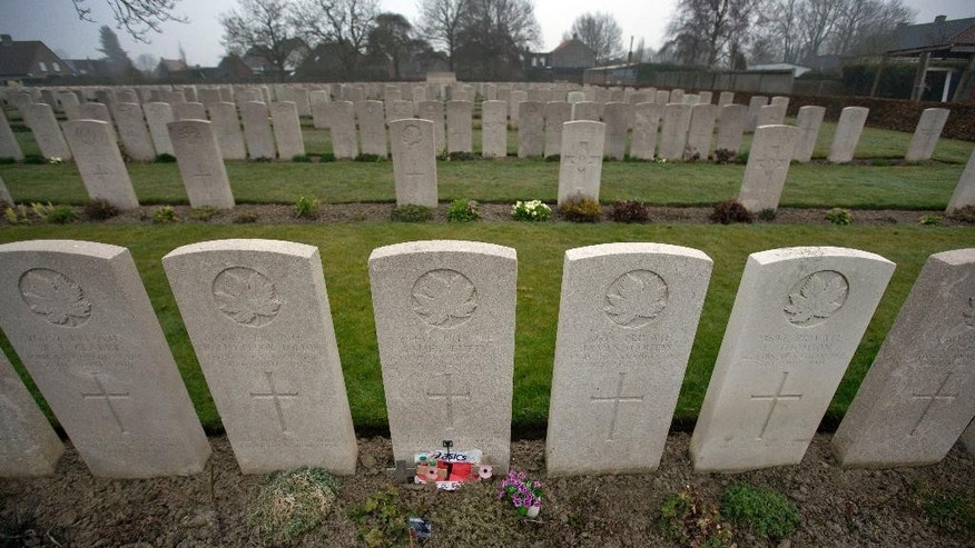 This photo taken on March 18, 2015 shows the grave of James Duffy, center, World War I soldier and Boston Marathon winner of 1914 at the Vlamertinghe Military Cemetery in Vlamertinge, Belgium. Duffy won the 1914 Boston Marathon and then died one year later, almost to the day, amid some of the worst violence of World War I. On Monday April 20, Maureen Kiesewetter will run the Boston Marathon in honor of her great-great uncle. (AP Photo/Virginia Mayo)