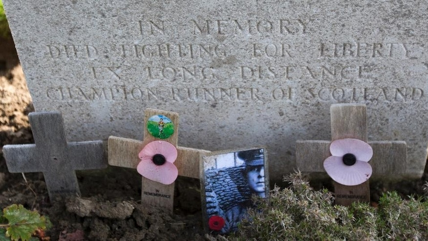 "In this photo taken on April 9, 2015, wooden crosses and a photo stand in front of an epitaph on the grave of James Duffy; World War I soldier and Boston Marathon winner of 1914, at the Vlamertinghe Military Cemetery in Vlamertinge, Belgium. Duffy was wounded by shrapnel during the first gas attacks of April 1915 and later died of his wounds. The epitaph reads ""In memory, died fighting for liberty. Ex long distance champion runner of Scotland. (AP Photo/Virginia Mayo)"