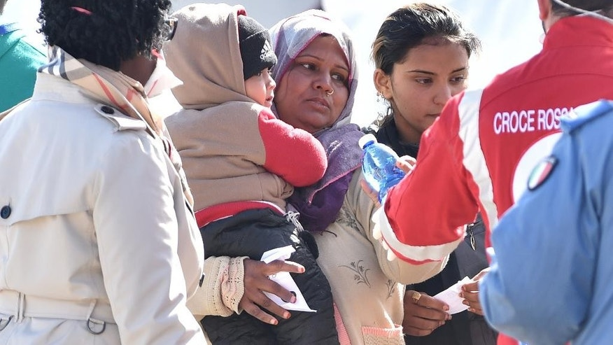 "Migrants receive first aid upon disembarking from Italian Navy ship ""Driade"" in Messina's port, Sicily, Italy, Saturday, April 18, 2015. Italian ships have picked up some 10,000 people, many of them refugees of war and persecution, over the past week, an unprecedented number in such a short period. The influx is putting pressure on Italy's shelter system and raising calls for a better response to the emergency. (AP Photo/Carmelo Imbesi)"