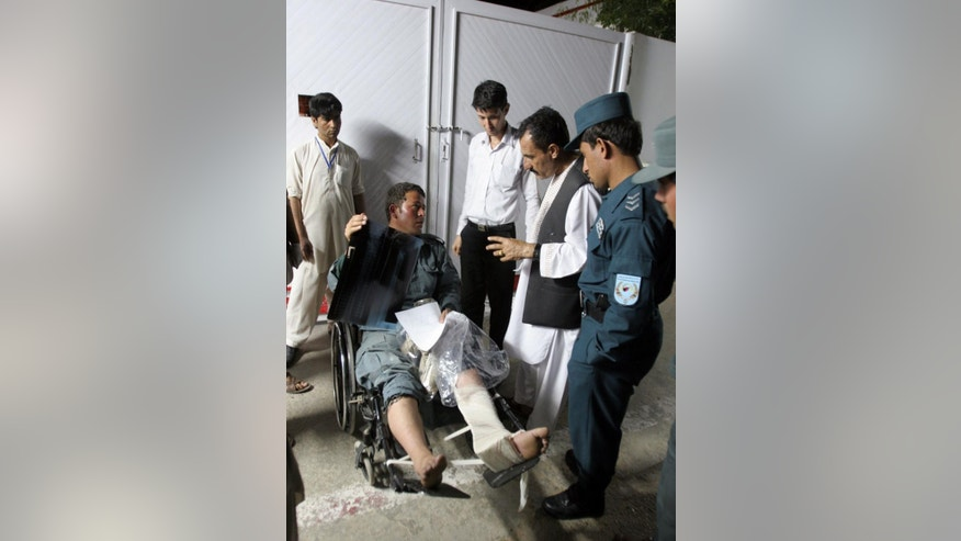 An Afghan injured policeman receives treatment as he sits in a wheelchair, at Lashkar Gah Hospital, after a suicide attack in the city of Lashkar Gah, capital of Helmand Province southern of Kabul, Afghanistan, Sunday, April, 19, 2015. Insurgents armed with guns and explosives entered a police station in Afghanistan's southern city of Lashkar Gah on Sunday after a suicide bomber detonated explosives at the gate of the compound allowing the others to gain entry, a senior policeman said. (AP Photo/Abdul Khaliq)
