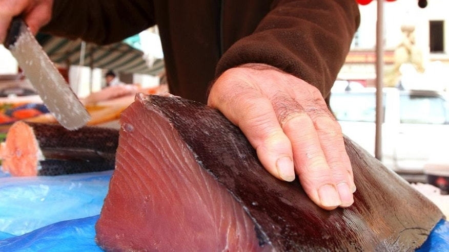 FILE - In this Feb. 4, 2010 file photo, a fishmonger cuts a joint of Bluefin tuna, which was caught off Thailand, at a stall at the Nice fish market, southeastern France. In a decision, to be officially announced on Tuesday, April 21, 2015, the European Union is to give Thailand six months to drastically change its policies on illegal and unregulated fishing or face an EU fish import ban at the end of the year. (AP Photo/Lionel Cironneau, File)