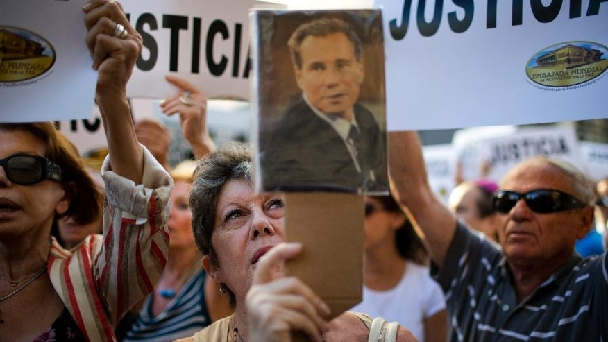 FILE - In this Jan. 21, 2015, file photo, a woman chants the Argentine national anthem holding a portrait of the late prosecutor Alberto Nisman outside the AMIA Jewish community center in Buenos Aires, Argentina. Nisman who accused the government of secret deals with Iran over the investigation was found shot dead at his apartment early Monday, Jan. 19, 2015. An Argentine prosecutor has dismissed the accusations made by Nisman against President Cristina Fernandez that she helped shield Iranian officials allegedly behind the 1994 bombing of a Jewish community center. (AP Photo/Rodrigo Abd, File)