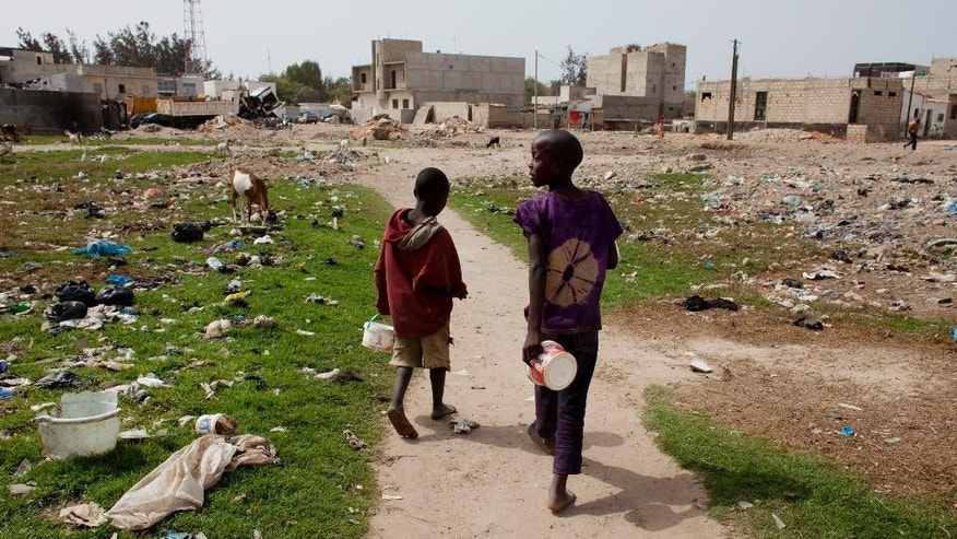 Talibe students walk in a field littered with garbage, holding the buckets from which they ate a lunch of rice and fish in Guediawaye, a suburb on the outskirts of of Dakar, Senegal,  Monday, April 20, 2015. They need to find more food before returning to school so they don't get beaten. Human Rights Watch and a coalition of 40 organizations in Senegal are calling on the government and police to enforce laws adopted nearly a decade ago that prohibit forcing children to beg. The groups issued a report Monday that said more than 30,000 Muslim boys who are sent to Quranic schools in Dakar region are exploited by teachers and forced to beg for food and money. (AP Photo/Jane Hahn)