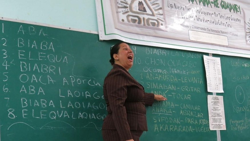 "In this April 10, 2015 photo, Wanda Ivette Diaz enunciates the Arawakan word for, ""touch"" during a language class for children, in San Lorenzo, Puerto Rico. In Puerto Rico's misty, bamboo-studded mountains, elementary school students are studying a nearly extinct language, beating on drums and growing native crops like cassava and sweet potato as they learn about the indigenous people who lived on the island before Christopher Columbus. (AP Photo/Danica Coto)"