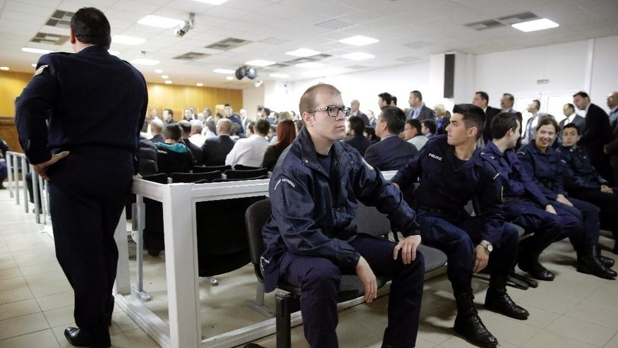 Police offices sit in front of suspects at the start of a trial of dozens of members and volunteers of the far-right Golden Dawn party, at Korydallos, near Athens, Monday April 20, 2015. Leaders of Greece's third-largest political party, the extreme right Golden Dawn, went on trial Monday on charges of operating as a criminal organization that allegedly carried out a campaign of violence against immigrants and left-wing opponents. (AP Photo/Petros Giannakouris)