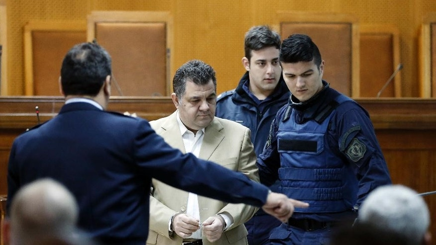 Police officers lead suspect Giorgos Roupakias at the start of a trial of dozens of members and volunteers of the far-right Golden Dawn party, at Korydallos, near Athens, Monday April 20, 2015. Leaders of Greece's third-largest political party, the extreme right Golden Dawn, went on trial Monday on charges of operating as a criminal organization that allegedly carried out a campaign of violence against immigrants and left-wing opponents. (AP Photo/Petros Giannakouris)