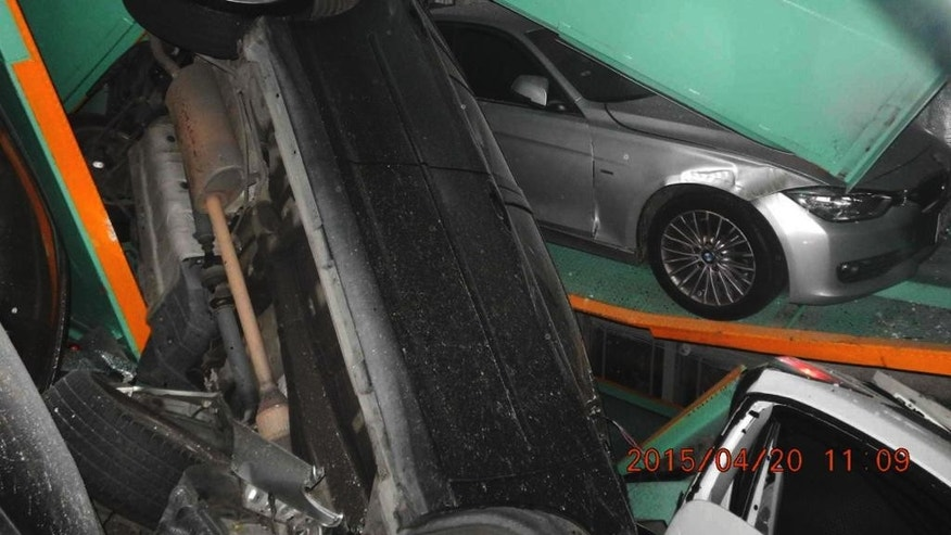 In a photo provided by the Taipei Fire Department, vehicles are seen piled on themselves in an automated parking tower after the lift system failed during the 6.3 magnitude earthquake that struck off the island's eastern coast in Taipei, Taiwan, Monday, April 20, 2015. No injuries resulted in the accident. The date that this photo was taken, seen in bottom right, is from the camera of the Taipei Fire Department. (Taipei Fire Department via AP)