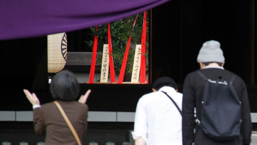 Religious offering dedicated by Japanese Prime Minister Shinzo Abe are seen, center in the background, as people pray at the Yasukuni Shrine in Tokyo during an annual spring festival Tuesday, April 21, 2015. Abe sent religious offerings Tuesday to the shrine that honors convicted World War II leaders among its war dead.  Abe's offerings likely signal that he will not pray at the controversial shrine ahead of trips to Asia and the United States. (AP Photo/Koji Ueda)