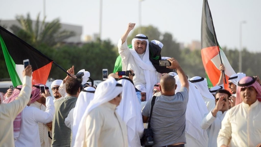 """Supporters celebrate with leading opposition leader Musallam al-Barrack after his release on bail ahead of a final decision on charges he insulted the country's ruler, in Kuwait City on Monday, April 20, 2015. The case against al-Barrack stems from a speech he gave during a rally in 2012. He called on Kuwait's ruling emir, Sheikh Sabah Al Ahmed Al Sabah, not to """"drag the country into a dark abyss,"""" and said Kuwait risked becoming an autocratic state.(AP Photo)"""