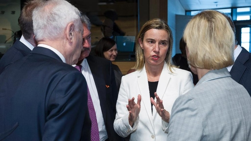 European Union High Representative Federica Mogherini, center, speaks with EU foreign ministers during a meeting at the EU Council building in Luxembourg on Monday, April 20, 2015. An Italian coast guard ship headed toward Sicily Monday to look for survivors of a capsized ship in what could be the Mediterranean's deadliest migrant tragedy, as EU foreign ministers gathered for an emergency meeting to discuss the crisis. Front left is Spanish Foreign Minister Jose Manuel Garcia-Margallo and front right is Swedish Foreign Minister Margot Wallstrom. (AP Photo/Thierry Monasse)