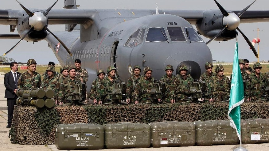 Lebanese army soldiers stand in front of French weapons at the Rafik Hariri International Airport in Beirut, Lebanon, Monday, April 20, 2015. Lebanon has received the first shipment of $3 billion worth of French weapons paid for by Saudi Arabia. The handover ceremony occurred Monday at Beirut's international airport and was attended by Lebanese, French defense ministers, and top army officers. (AP Photo/Bilal Hussein)