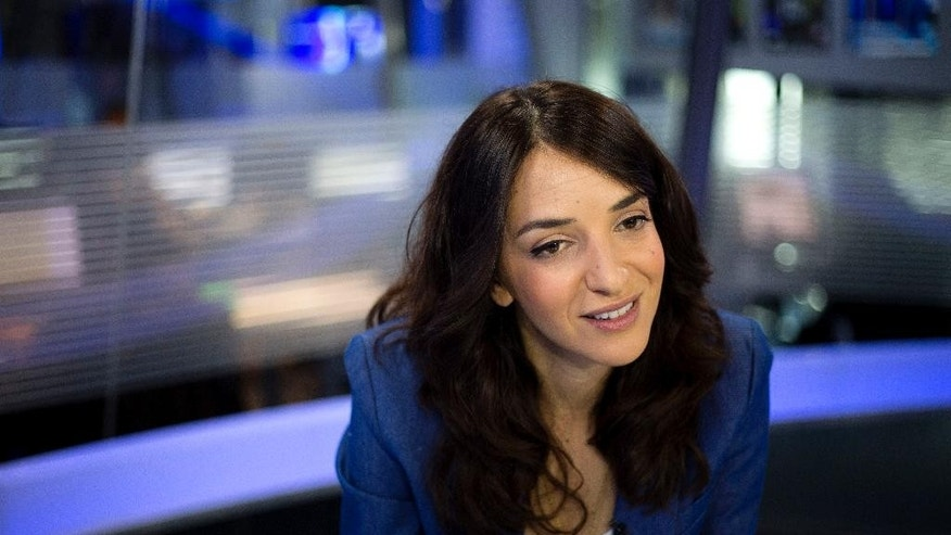 "In this Sunday, April 13, 2015 photo, Arab newscaster Lucy Aharish speaks during an interview with The Associated Press in Tel Aviv, Israel. The 34-year-old journalist will be challenging some of her Arab compatriots who commemorate Israel's independence day as ""the catastrophe,"" when many Arabs were uprooted from their homes in the 1948 war surrounding Israel's founding. She also will be thumbing her nose at some Jews who believe she doesn't deserve the honor. (AP Photo/Ariel Schalit)"