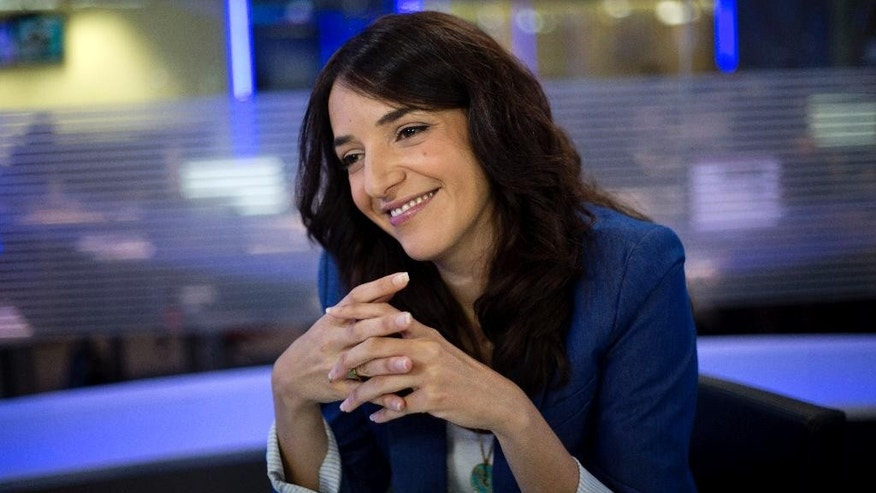 "In this Sunday, April 13, 2015 photo, Arab newscaster Lucy Aharish smiles during an interview with The Associated Press in Tel Aviv, Israel. The 34-year-old journalist will be challenging some of her Arab compatriots who commemorate Israel's independence day as ""the catastrophe,"" when many Arabs were uprooted from their homes in the 1948 war surrounding Israel's founding. She also will be thumbing her nose at some Jews who believe she doesn't deserve the honor. (AP Photo/Ariel Schalit)"