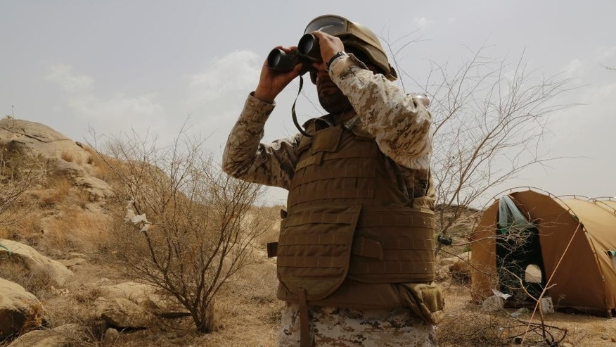 A Saudi soldier looks with binoculars toward the border with Yemen in Jazan, Saudi Arabia, Monday, April 20, 2015. The Saudi air campaign in Yemen is now in its fourth week. (AP Photo/Hasan Jamali)