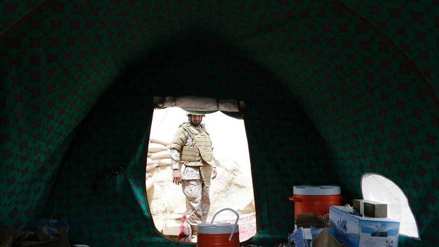 A Saudi soldier is seen through a tent positioned at the Saudi border with Yemen in Jazan, Saudi Arabia, Monday, April 20, 2015. The Saudi air campaign in Yemen is now in its fourth week.(AP Photo/Hasan Jamali)