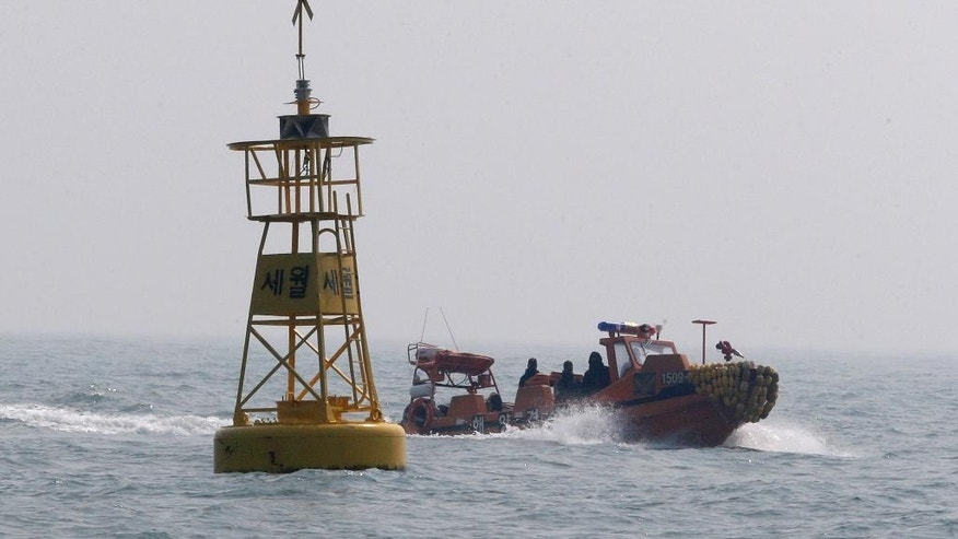 "In this Wednesday, April 15, 2015 photo, a South Korea Coast Guard boat passes a buoy, which marks the site where the ferry Sewol sank off Jindo, South Korea. South Korea's oceans ministry says it's ready to start works to salvage a ferry that sank last year, killing more than 300 people. The letters at a buoy read "" Sewol.""(AP Photo/Ahn Young-joon)"