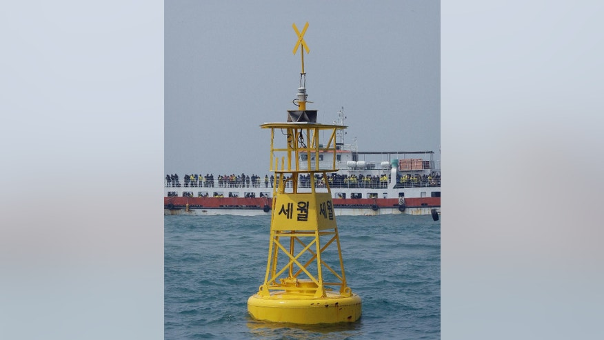 "In this Wednesday, April 15, 2015, photo, a passenger ship with family members of the victims of the ferry Sewol sinking passes a buoy, which marks the site where the ship sank off Jindo, South Korea. South Korea's oceans ministry says it's ready to start works to salvage a ferry that sank last year, killing more than 300 people. The letters at a buoy read "" Sewol.""(AP Photo/Ahn Young-joon)"