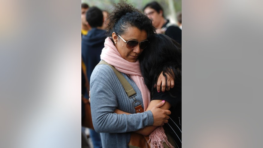 A woman comforts a young girl after a student walked into a Barcelona school Monday morning and killed a teacher and wounded several other high school students on the 16th anniversary of the massacre of students in shootings at Columbine High School in the U.S. state of Colorado. (AP Photo/Emilio Morenatti)