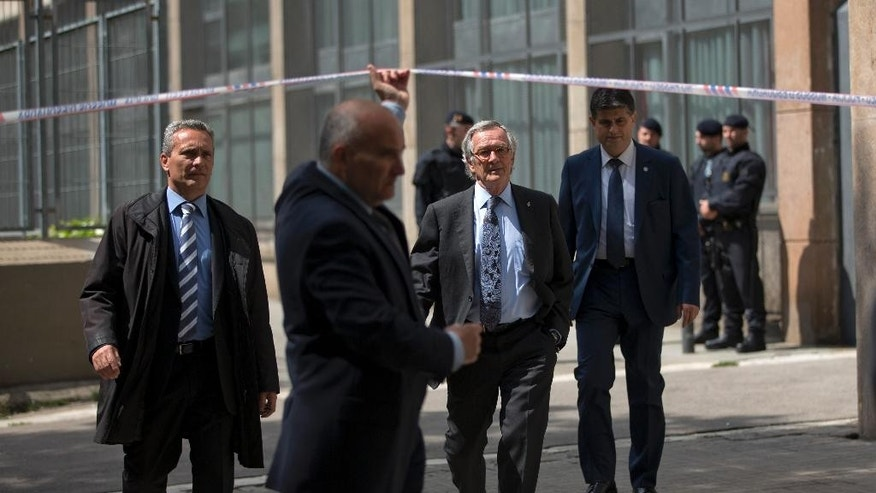 The Mayor of Barcelona Xavier Trias, center, leaves after visiting the school in Barcelona, Spain, Monday, April 20, 2015. A student walked into a Barcelona school Monday morning and killed a teacher and wounded several other high school students on the 16th anniversary of the massacre of students in shootings at Columbine High School in the U.S. state of Colorado. (AP Photo/Emilio Morenatti)